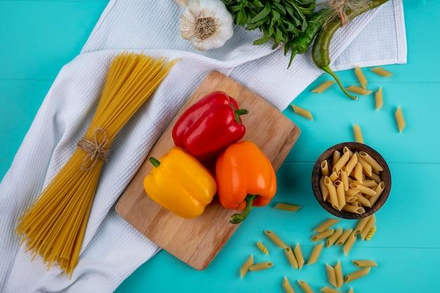 Bovenaanzicht van gekleurde paprika op een snijplank met rauwe pasta en spaghetti op een turkoois oppervlak