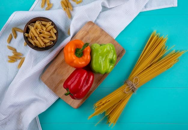 Bovenaanzicht van gekleurde paprika op een snijplank met rauwe spaghetti en pasta op een turkoois oppervlak