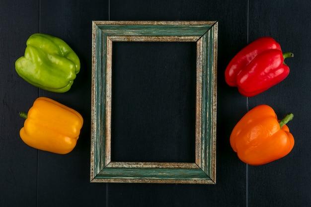 Bovenaanzicht van gekleurde paprika's met een groenachtig geel frame op een zwarte ondergrond