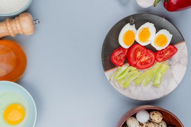 Bovenaanzicht van gekookt ei op een plaat met plakjes tomaten met kwarteleitjes op een houten kom op een witte achtergrond met kopie ruimte