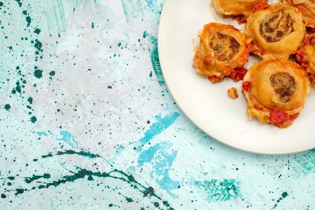 Bovenaanzicht van gekookte deegmaaltijd met gehakt binnen plaat op helder