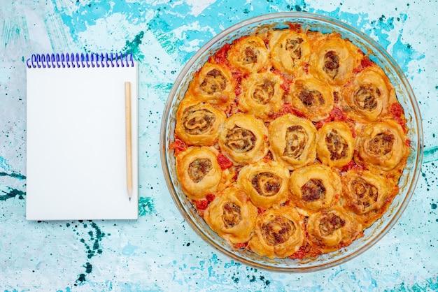 Bovenaanzicht van gekookte deegmaaltijd met gehakt en tomatensaus in glazen pan met blocnote op helderblauw, koken bakken voedsel vleesdeeg