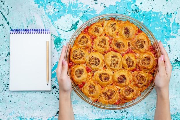Bovenaanzicht van gekookte deegmaaltijd met gehakt en tomatensaus in glazen pan met ntoepad op helderblauw, koken bakvoedsel vleesdeeg