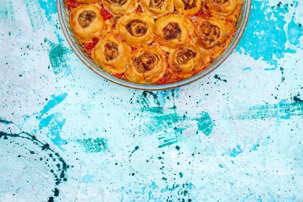 Bovenaanzicht van gekookte deegmaaltijd met gehakt en tomatensaus in glazen pan op helderblauw bureau, bak voedsel vleesdeeg