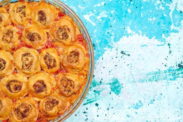Bovenaanzicht van gekookte deegmaaltijd met gehakt en tomatensaus in glazen pan op helderblauw bureau, koken bakken voedsel vleesdeeg