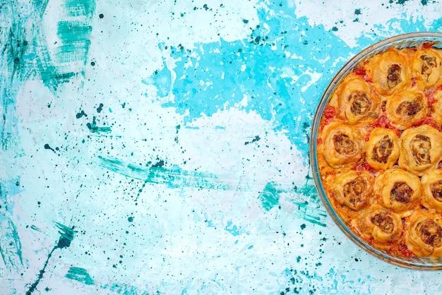 Bovenaanzicht van gekookte deegmaaltijd met gehakt en tomatensaus in glazen pan op helderblauw, koken bakken voedsel vleesdeeg