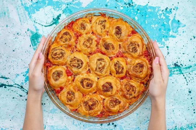 Bovenaanzicht van gekookte deegmaaltijd met gehakt vlees en tomatensaus in glazen pan nemen door vrouwtje op helderblauw bureau, koken bakken voedsel vleesdeeg