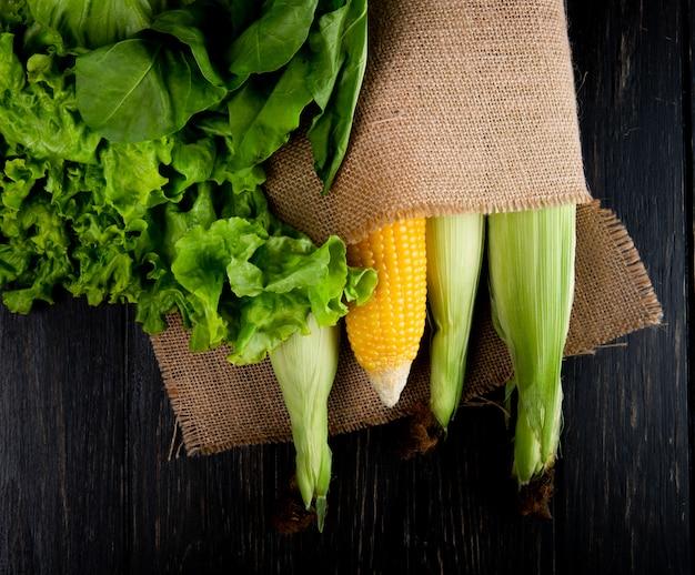 Bovenaanzicht van gekookte en ongekookte likdoorns in zak met sla en spinazie op zwart