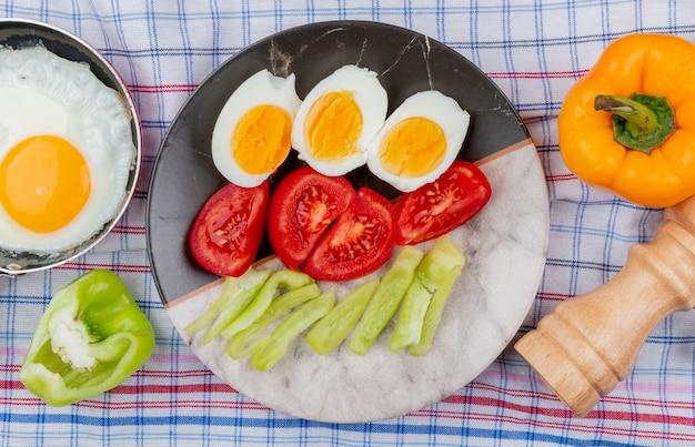 Bovenaanzicht van gekookte gehalveerde eieren op een bord met gehakte plakjes tomaten en groene paprika op een gecontroleerde tafellaken achtergrond