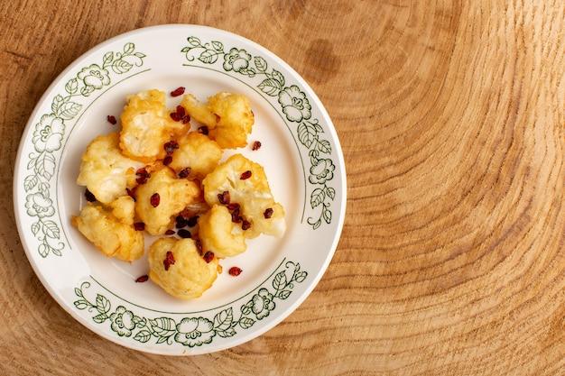 Bovenaanzicht van gekookte gesneden bloemkool in plaat op crème houten oppervlak