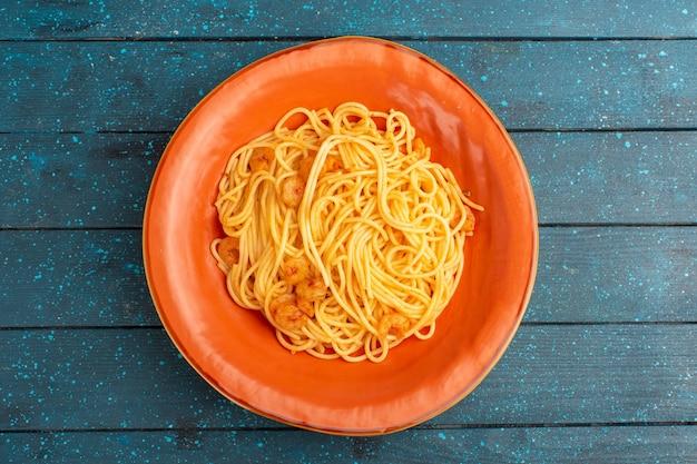 Bovenaanzicht van gekookte italiaanse pasta lekker in oranje plaat op het blauwe houten rustieke oppervlak