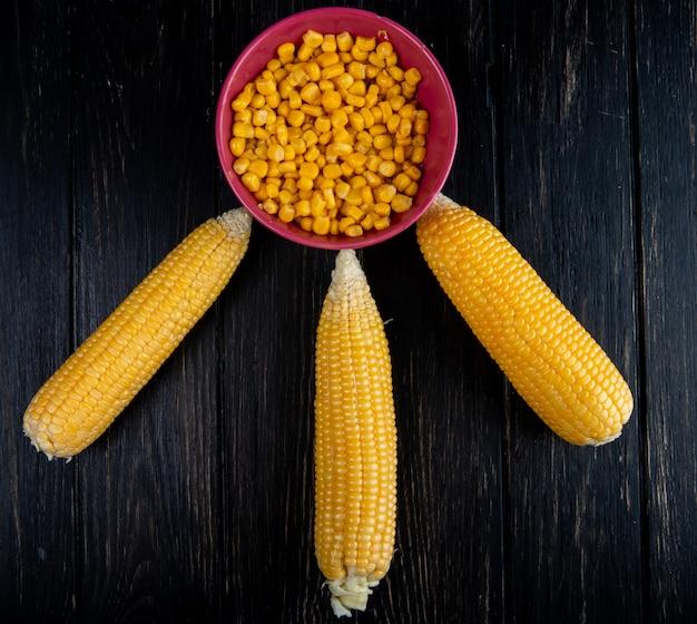 Bovenaanzicht van gekookte likdoorns met kom van gekookte maïs zaden op zwarte ondergrond
