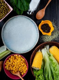 Bovenaanzicht van gekookte maïs maïs zaden lege plaat sla met maïs zijde zout lepel spinazie op zwart