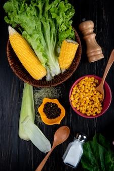Bovenaanzicht van gekookte maïs maïs zaden sla met maïs schelp en zijde zout lepel spinazie op zwart