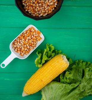 Bovenaanzicht van gekookte maïs met sla en lepel vol maïs zaden op groene ondergrond