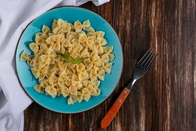 Bovenaanzicht van gekookte pasta op een blauw bord met een vork op een houten oppervlak