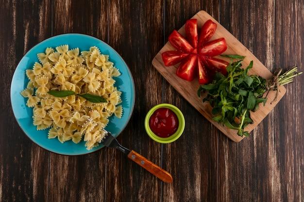 Bovenaanzicht van gekookte pasta op een blauw bord met een vork tomaten en een bosje munt op een snijplank met ketchup op een houten oppervlak