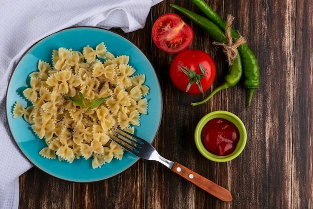 Bovenaanzicht van gekookte pasta op een blauw bord met een vork tomatenketchup en chilipepers op een houten oppervlak