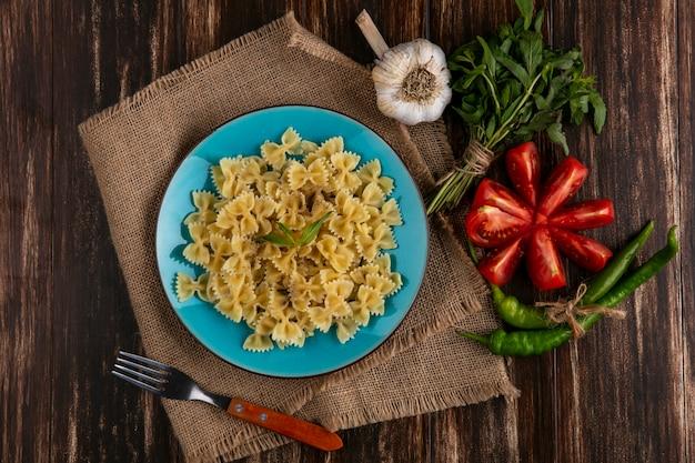 Bovenaanzicht van gekookte pasta op een blauw bord op een beige servet met een vork tomaten knoflook en chilipepers op een houten oppervlak