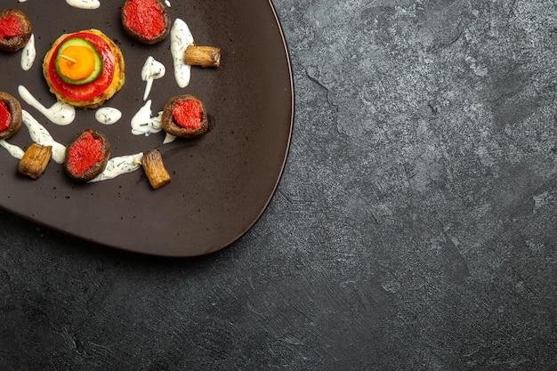 Bovenaanzicht van gekookte pompoenen ontworpen maaltijd binnen plaat op het grijze oppervlak