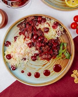 Bovenaanzicht van gekookte rijst met vlees en kersen