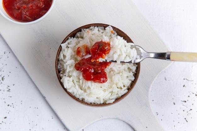 Bovenaanzicht van gekookte rijst smakelijke maaltijd in bruine pot met rode pikante saus op witte ondergrond