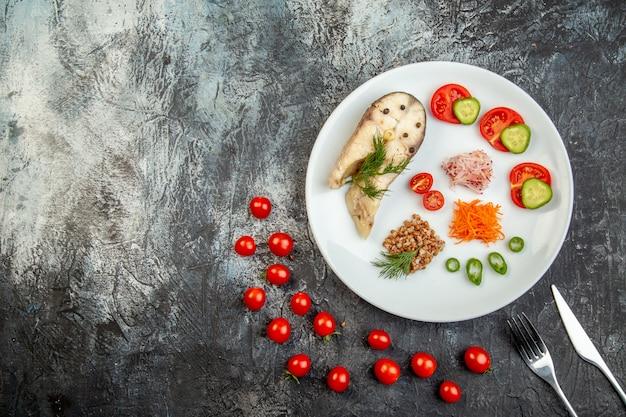 Bovenaanzicht van gekookte visboekweit geserveerd met groenten groen op een wit bord en bestek op ijsoppervlak met vrije ruimte