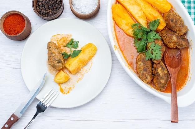 Bovenaanzicht van gekookte vleeskoteletten met pittige sausaardappelen en groene kruiderijen op licht bureau, voedsel maaltijd vlees groente