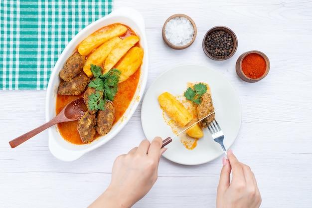 Bovenaanzicht van gekookte vleeskoteletten met sausaardappelen en groen krijgen eten door vrouwtje op licht bureau, voedsel maaltijd vlees groente