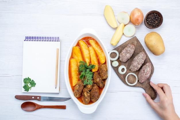 Bovenaanzicht van gekookte vleeskoteletten met sausaardappelen en groen samen met rauw vlees op licht bureau, voedsel maaltijd vlees groente