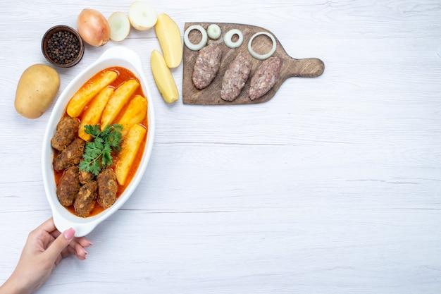 Bovenaanzicht van gekookte vleeskoteletten met sausaardappelen en groen samen met rauw vlees op lichte, voedselmaaltijd vleesgroente