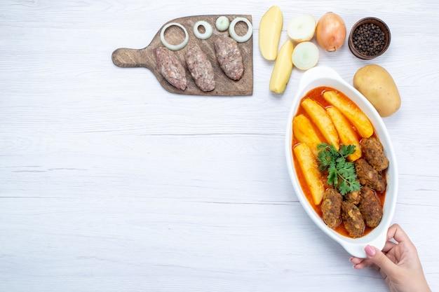 Bovenaanzicht van gekookte vleeskoteletten met sausaardappelen en groenen samen met rauw vlees op licht bureau, voedsel maaltijd vlees groente