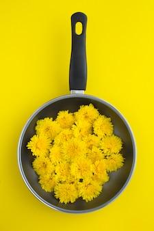 Bovenaanzicht van gele bloemen in een koekenpan op geel