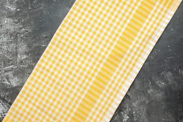 Bovenaanzicht van gele handdoek op grijze ondergrond
