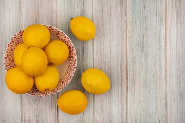 Bovenaanzicht van gele huid hele citroenen op een kom met citroenen geïsoleerd op een grijze houten oppervlak met kopie ruimte
