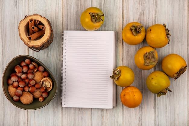 Bovenaanzicht van gele kaki fruit met hazelnoten en walnoten op een kom op een grijze houten tafel met kopie ruimte