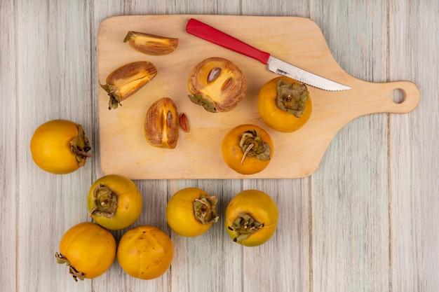 Bovenaanzicht van gele kaki vruchten op een houten keukenplank met mes op een grijze houten tafel