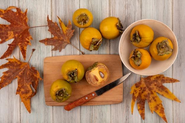 Bovenaanzicht van gele kaki vruchten op een kom met bladeren met kaki vruchten op een houten keukenplank met mes op een grijze houten tafel