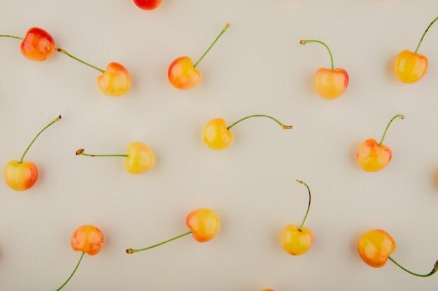 Bovenaanzicht van gele kersen op witte ondergrond