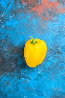 Bovenaanzicht van gele paprika op blauwe ondergrond