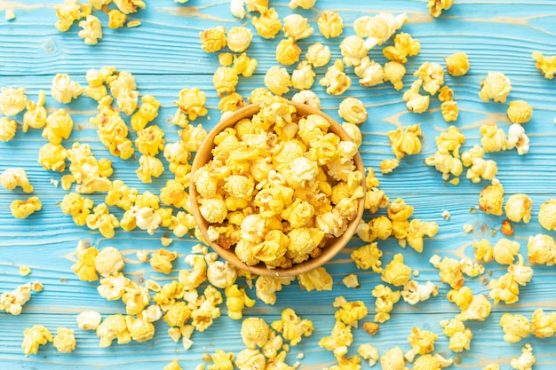 Bovenaanzicht van gele popcorn op blauwe houten planken