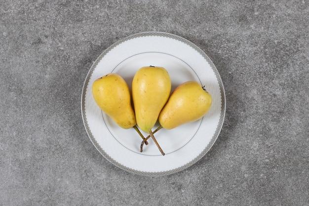 Bovenaanzicht van gele rijpe peren op witte plaat.
