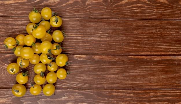 Bovenaanzicht van gele tomaten aan de linkerkant en houten tafel