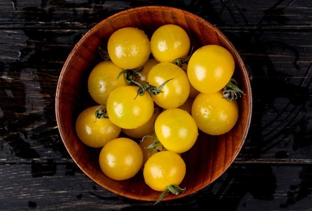 Bovenaanzicht van gele tomaten in kom op houten tafel
