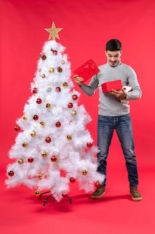 Bovenaanzicht van gelukkig knappe volwassene in een grijze blouse staande in de buurt van de versierde witte kerstboom