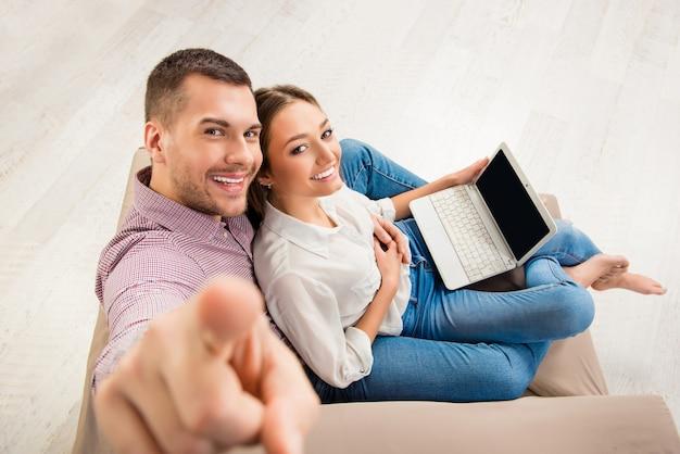 Bovenaanzicht van gelukkig man en vrouw zittend op de bank met laptop, man camera aan te raken