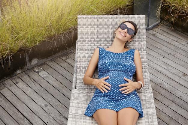 Bovenaanzicht van gelukkige aanstaande moeder in tinten en blauwe jurk rust op een ligstoel, houdt haar dikke buik vast en voelt zich verbonden met haar ongeboren kind.