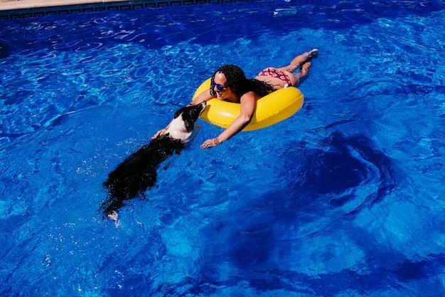 Bovenaanzicht van gelukkige blanke vrouw ontspannen op gele donuts opblaasbaar bij zwembad. leuke border collie-hond in het zwembad. zomertijd, vakantie en levensstijl
