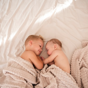 Bovenaanzicht van gelukkige broers en zussen binnenshuis