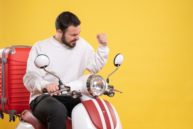 Bovenaanzicht van gelukkige jonge kerel zittend op motorfiets met koffer erop op geïsoleerde gele achtergrond on